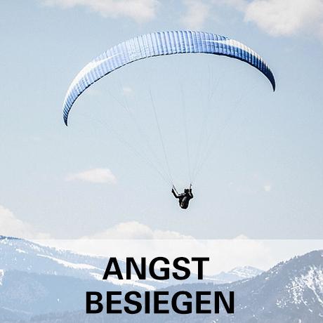 Bild zum Thema Angst besiegen - Mann frei mit Paraglider und Bergen